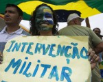 """A woman shows a placard reading """"Military intervention"""" during a protest against Brazil's President Dilma Rousseff in Manaus, Amazonas state March 15, 2015. Protest organizers in dozens of cities across Brazil are planning marches to pressure Rousseff over unpopular budget cuts and a corruption scandal that has snared leaders of her political coalition. REUTERS/Bruno Kelly  (BRAZIL - Tags: POLITICS CIVIL UNREST)"""