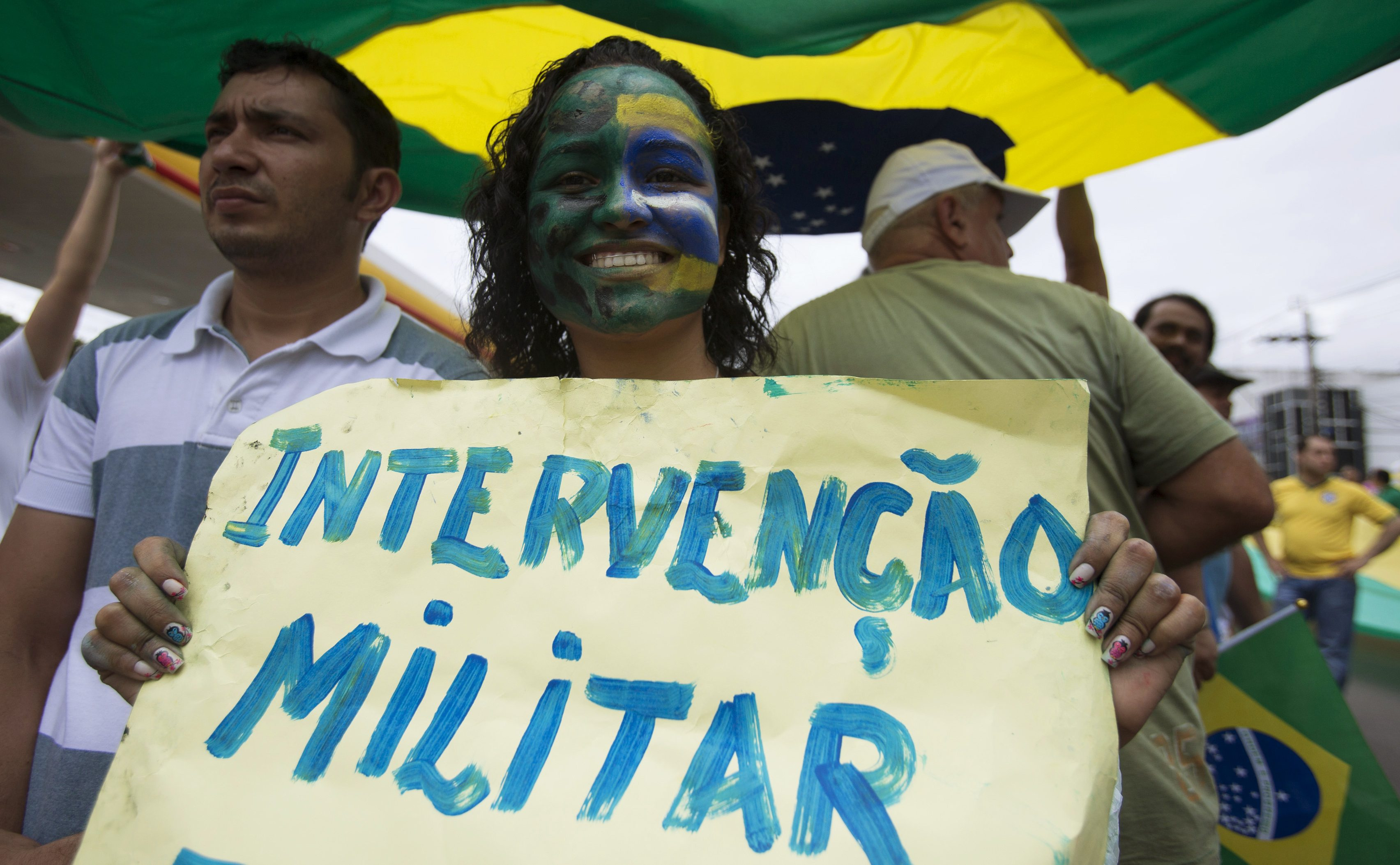 "A woman shows a placard reading ""Military intervention"" during a protest against Brazil's President Dilma Rousseff in Manaus, Amazonas state March 15, 2015. Protest organizers in dozens of cities across Brazil are planning marches to pressure Rousseff over unpopular budget cuts and a corruption scandal that has snared leaders of her political coalition. REUTERS/Bruno Kelly  (BRAZIL - Tags: POLITICS CIVIL UNREST)"