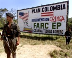SAN VICENTE, COLOMBIA:  Two guerrillas of the Revolutionary Armed Forces of Colombia (FARD) stand guard on a highway next to a billboard with propaganda against the US-backed Colombia Plan in San Vicente, Colombia 30 January 2001. AFP PHOTO/Luis ACOSTA (Photo credit should read LUIS ACOSTA/AFP/Getty Images)